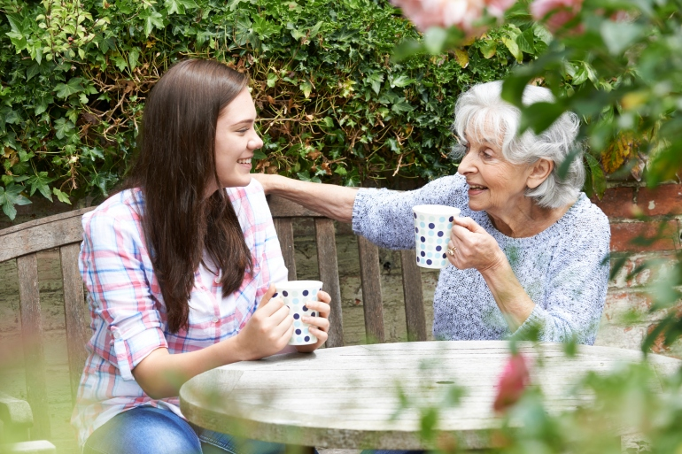 Teenage Granddaughter Relaxing With Grandmother In Garden